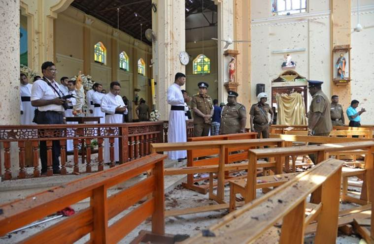 Police officials and catholic priests stand inside the church after a bomb blast in Negombo